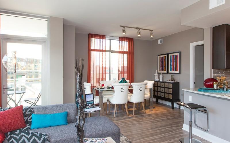natural light floods open concept apartment through large picture windows