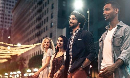 millennials walking through bustling downtown at night